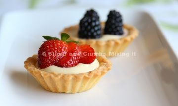 Strawberry tart and blackberry tart served on a white dish